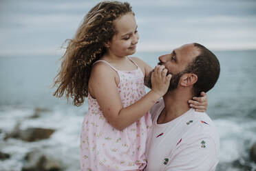 Daughter smiling while looking at father on shore - GMLF00324
