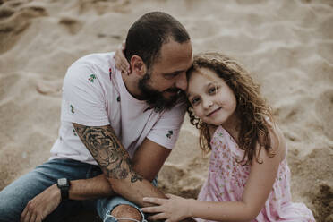 Smiling daughter sitting with father on sand at beach - GMLF00327