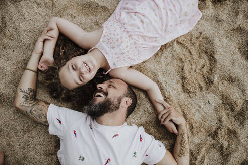 Father embracing daughter while sitting on beach - GMLF00330