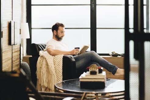 Mature man sitting barefoot in armchair, reading bok - DGOF01093