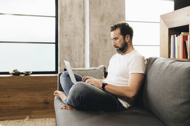 Mature man sitting on couch, using laptop - DGOF01099