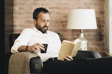 Mature man sitting in armchair, reading book, drinking coffee - DGOF01120