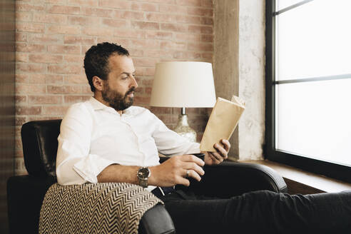 Mature man sitting in armchair by window, reading book - DGOF01123