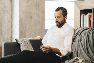 Mature man sitting on couch, using digital tablet - DGOF01138
