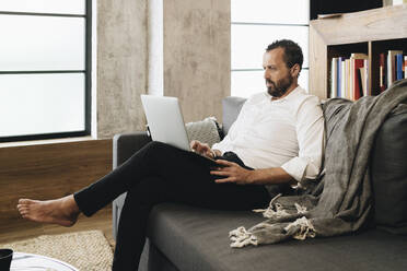 Mature man sitting on couch, using laptop - DGOF01141