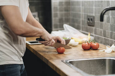 Mature man standing in kitchen, slicing tomatoes - DGOF01147