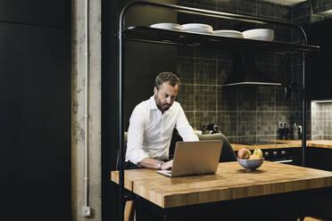 Mature businessman working in kitchen, using laptop - DGOF01165