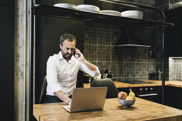 Mature businessman working in kitchen, using laptop, talking on the phone - DGOF01168