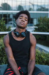 Portrait of a confident young man with headphones sitting in the city - JMPF00038
