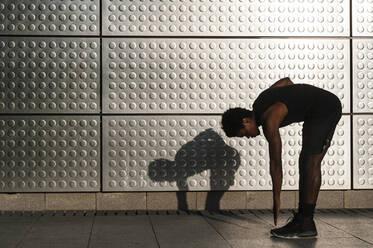 Young man exercising at a metallic shining wall - JMPF00041