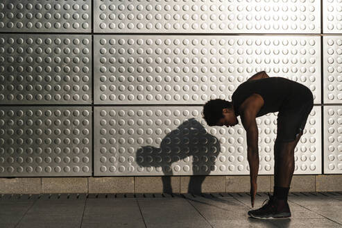 Young man exercising at a metallic shining wall - JMPF00041