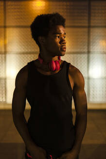 Portrait of a young man with headphones at night with city lights - JMPF00050