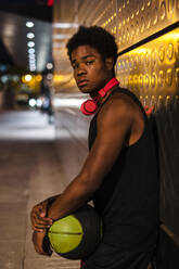 Portrait of a young man holding basketball at night in the city - JMPF00053