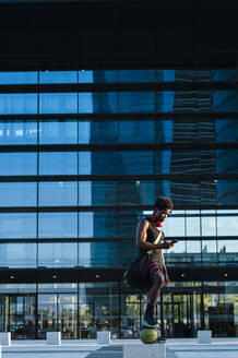 Young man with basketball and smartphone at a modern building in the city - JMPF00059
