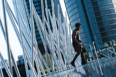 Young man playing basketball in modern city surrounding - JMPF00062