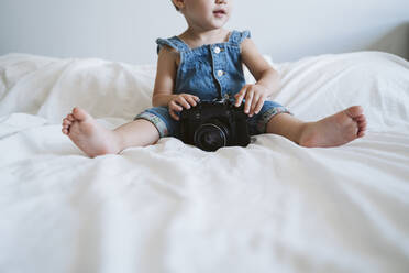 Baby girl holding camera at home - EBBF00355
