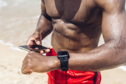 Athletic man with smartphone and smartwatch at beach - OCMF01413