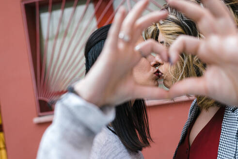 Close-up of lesbian couple making heart shape with hands while kissing in city - JMPF00079
