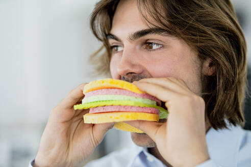 Close-up of businessman looking away while eating sponge cloth burger in cafe - KNSF08103