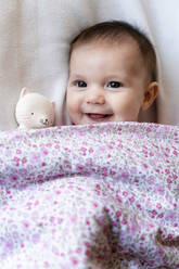 Portrait of happy baby girl lying on bed with teether - GEMF03892