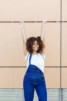 Cheerful young woman with arms raised standing against wall in city - JSMF01560