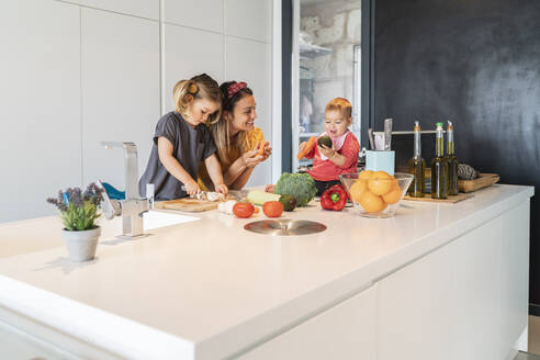 Baby girl sitting on island while mother and daughter preparing food in kitchen - JAF00016