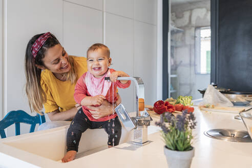 Smiling mother holding cute baby daughter playing with faucet in kitchen sink - JAF00019