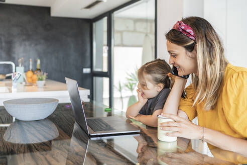 Mother with daughter looking at laptop while talking over smart phone in house - JAF00034