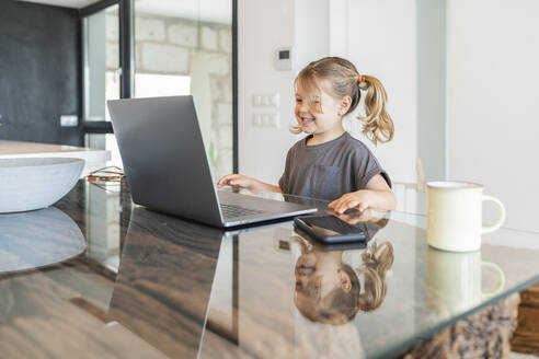 Smiling cute girl studying over laptop on table at home - JAF00037