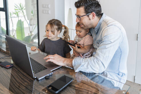 Mid adult man working over laptop with taking care of daughters at home - JAF00040