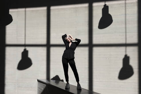 Stylish female professional wearing elegant suit sitting with sunlight and shadow in background at office - TCEF00816