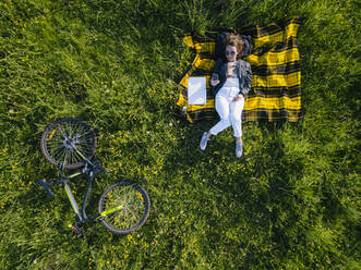 Aerial view of young woman at the green lawn, Tikhvin, Russia - KNTF04732