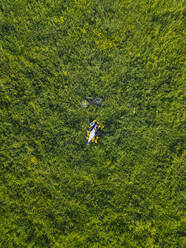 Aerial view of young woman at the green lawn, Tikhvin, Russia - KNTF04735