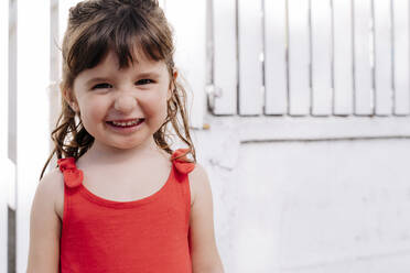 Portrait of little girl wearing red summer dress in front of white wall - GEMF03905