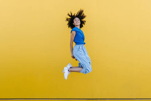 Pretty woman jumping for joy in front of yellow wall - TCEF00842
