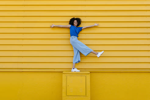Happy young woman balancing on platform in front of yellow wall - TCEF00851