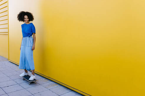 Young woman skateboarding in front of yellow wall - TCEF00857