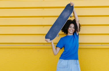 Smiling young woman holding skateboard aloft - TCEF00863