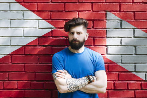 Young man with tattoo standing in front of red brick wall with arms crossed - EYAF01202
