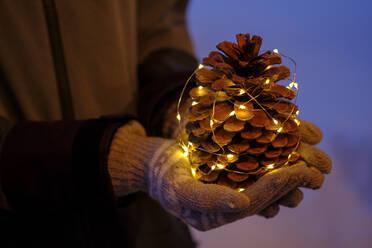 großer Pinienzapfen mit Lichterkette, auf Händen, Winterdekoration, Oberbayern, Bayern, Deutschland - LBF03129