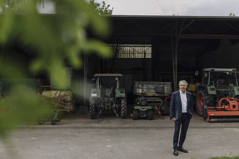Senior businessman standing on a farm with tractor in barn - GUSF04035