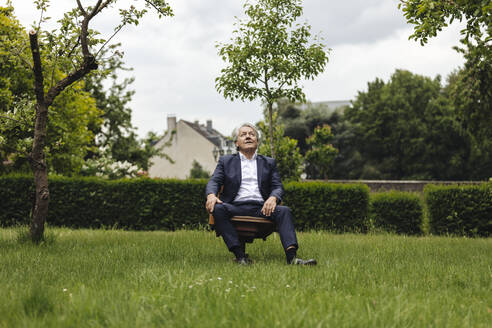 Senior businessman sitting on a chair in a rural garden looking up - GUSF04044