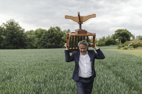 Senior businessman carrying a chair on a field in the countryside - GUSF04071