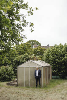 Senior businessman standing at a greenhouse - GUSF04074