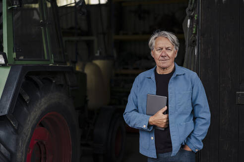 Portrait of a confident senior man holding tablet on a farm with tractor in barn - GUSF04122