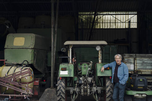 Portrait of a confident senior man on a farm with tractor in barn - GUSF04131