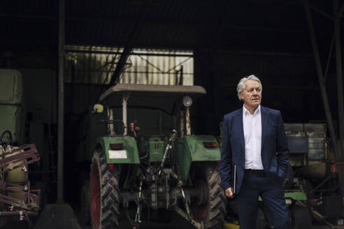 Senior businessman holding laptop on a farm with tractor in barn - GUSF04140