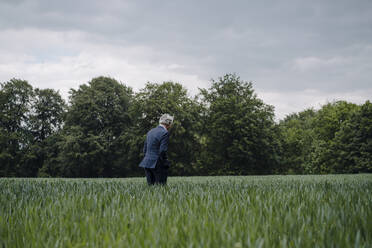 Senior businessman on a field in the countryside - GUSF04152