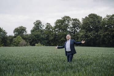 Senior businessman standing on a field in the countryside with outstretched arms - GUSF04155