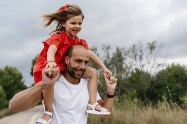 Happy man carrying daughter on shoulders at countryside - EGAF00359